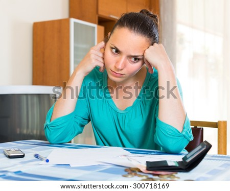 Young woman sits at table depressed because of bills   - stock photo