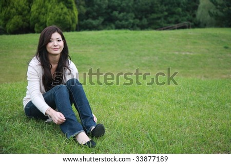 young woman sits down on a lawn