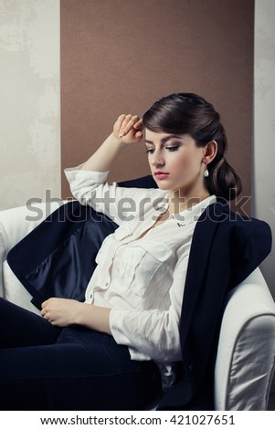 Young woman sits in a chair.