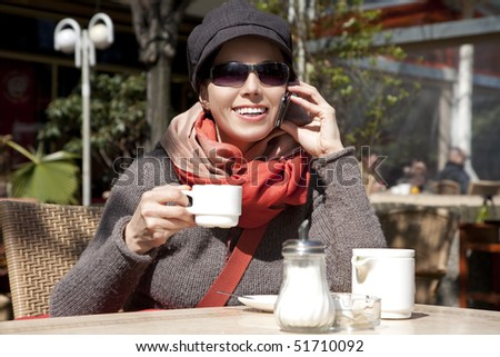 Young woman sits in the summer cafe and speaks by phone.