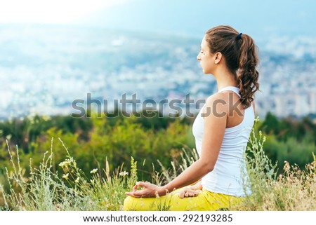 Young woman sits in yoga pose with city on background. Freedom concept. Calmness and relax, woman happiness. - stock photo