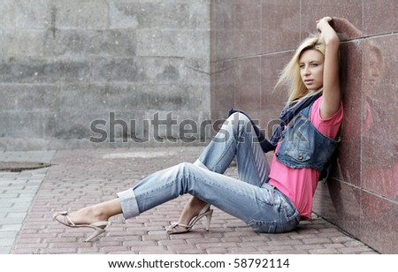 young woman sits near a wall on the street