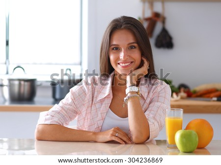 Young woman sitting a table  in the kitchen . - stock photo
