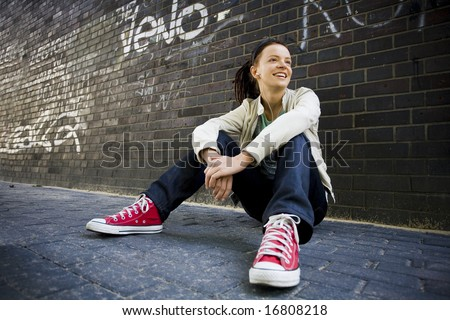 Young woman sitting against a brick wall - stock photo