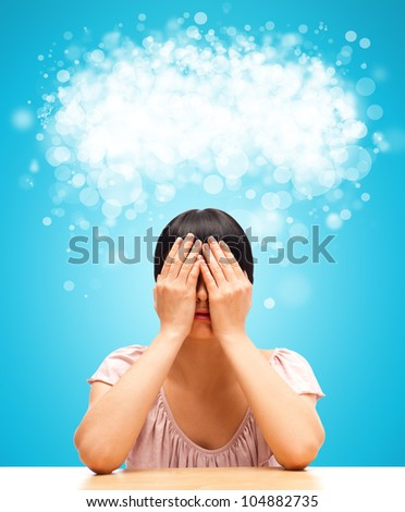 Young woman sitting against blue background with eyes closed by her hands. Blank cloud balloon with copyspace overhead - stock photo