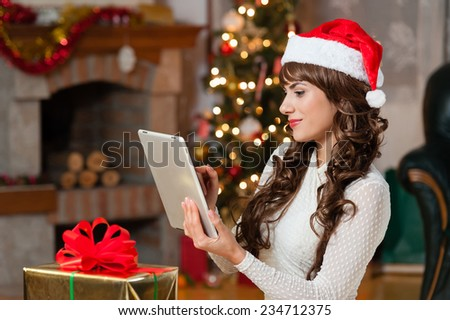 Young woman sitting alone with a red christmas hat, in front of christmas tree on living room,using tablet pc. - stock photo