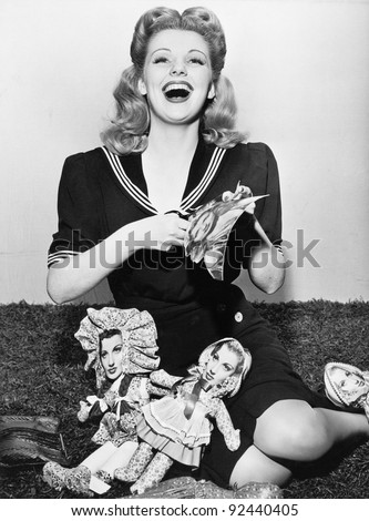 Young woman sitting and cutting out paper dolls - stock photo