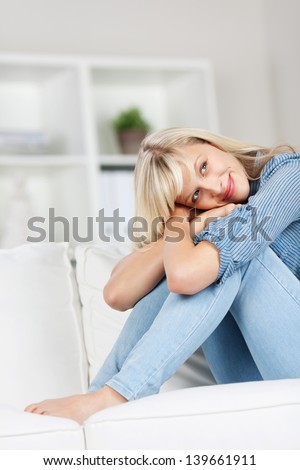 Young woman sitting and embracing her legs, isolated on a blurred background