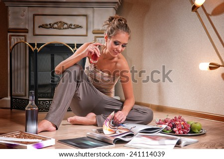 young woman sitting and reading magazine indoor shot  - stock photo