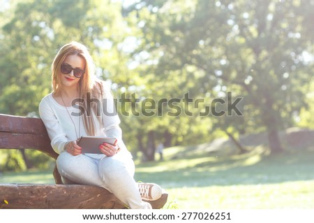 Young woman sitting and reading something on tablet - stock photo