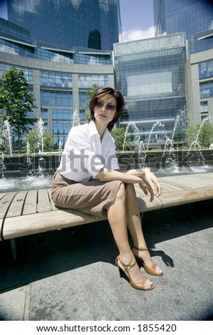 Young woman sitting and waiting on a bench at Coloumbus circle, Manhattan, New York, USA - stock photo