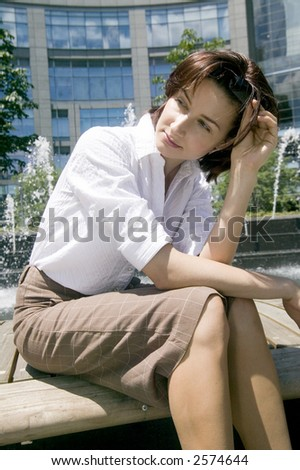 Young woman sitting and waiting on a bench at Columbus circle, Manhattan, New York, USA