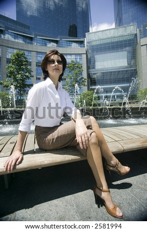 Young woman sitting and waiting on a bench at Columbus circle, Manhattan, New York, USA - stock photo
