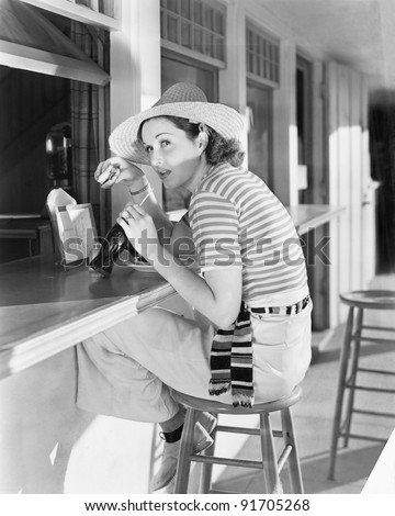 Young woman sitting at a counter drinking a coca cola - stock photo