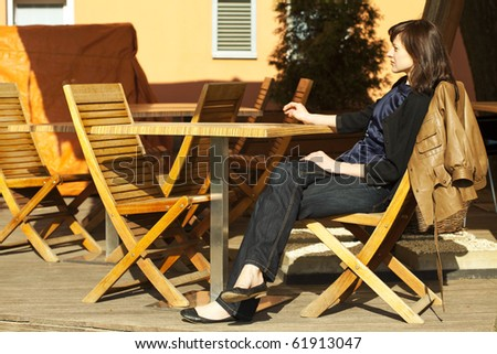 young woman sitting at a table in a cafe - stock photo