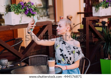 Young woman sitting at a table in a cafe, drinking coffee and doing selfie. Film processing.