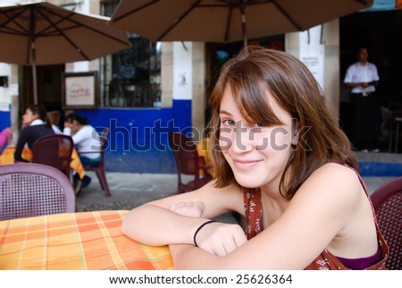 Young woman sitting at a table in an outdoor restaurant in Mexico. - stock photo