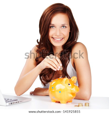 Young woman sitting at a table saving her change placing coins in a piggy bank as she saves for retirement or to pay for a dream to come true - stock photo