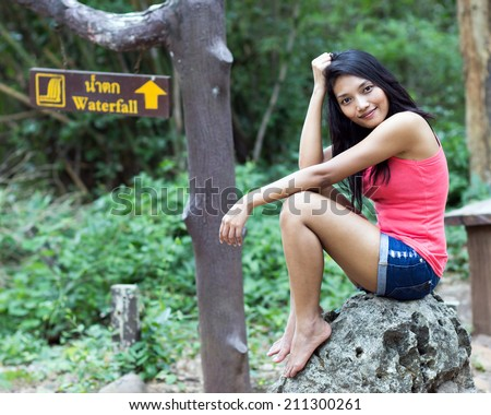 Young woman sitting at a waterfall Signs - stock photo