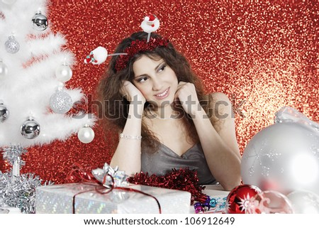 Young woman sitting at Christmas table surrounded by ornaments and gifts, smiling and thinking.