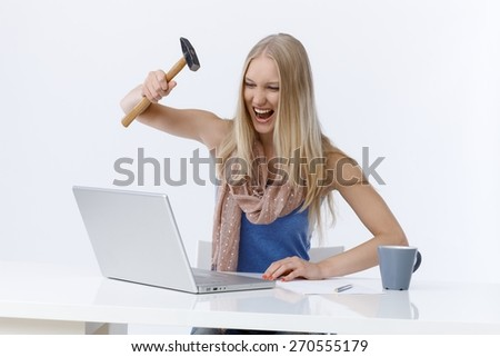 Young woman sitting at desk, attacking laptop computer by hammer, shouting angry. - stock photo