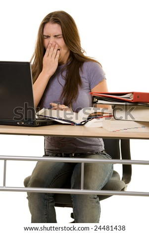 Young woman sitting at desk in front of laptop beside a pile of thick textbooks with hand over mouth yawning - stock photo