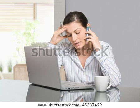 Young woman sitting at desk working with laptop computer at home, talking on mobile phone. - stock photo