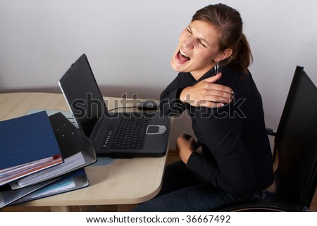 Young woman sitting at her laptop with a lot of work in front of her. She has a pain in her neck / back. - stock photo