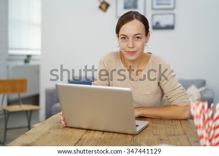 Young Woman, Sitting at her Wooden Office Desk with Laptop Computer, Looking at the Camera with Half Smile Face. - stock photo