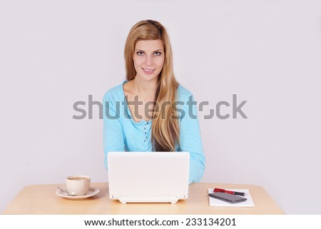 young woman sitting at home office desk with laptop computer and coffee