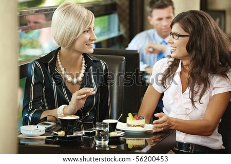Young woman sitting at table in cafe, drinking coffee eating cake, talking. - stock photo