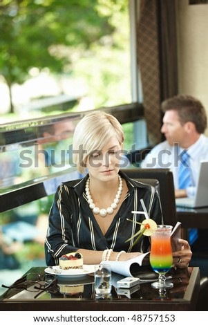 Young woman sitting at table in cafe, reading magazine. - stock photo