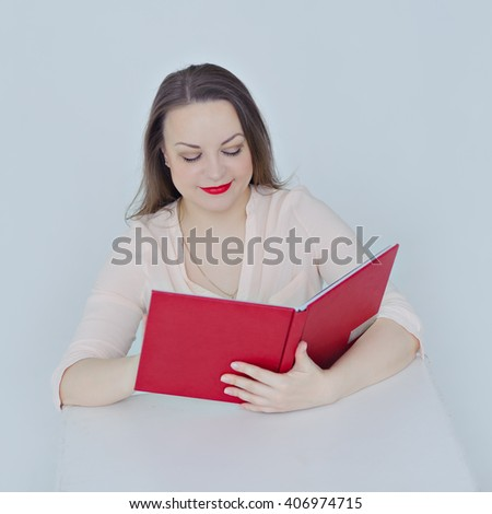 Young woman sitting at the table, holding and reading an open book red, smiling, gray background, close-up, square.