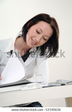 young woman sitting at the table in office and look to documents