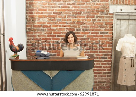 Young woman sitting behind a counter - stock photo