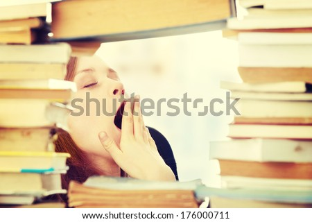 Young woman sitting behind books - tired