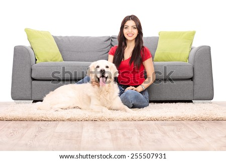 Young woman sitting by a sofa with her dog isolated on white background - stock photo