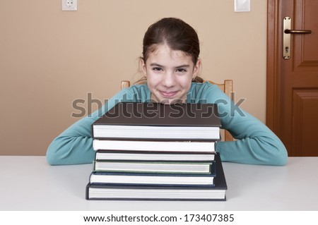 Young woman sitting by desk with books