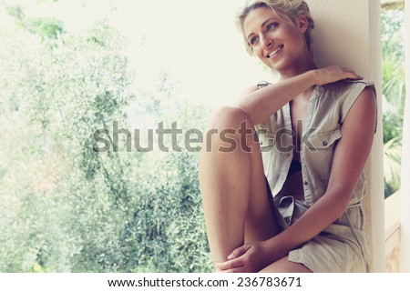 Young woman sitting by golden light in holiday villa. - stock photo
