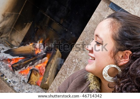 Young woman sitting by the fire during a game of cards - stock photo