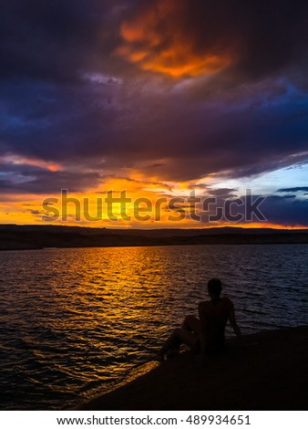 Young Woman sitting by the lake looking at Sunset