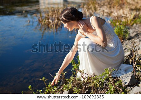 Young woman sitting by water and looking at her reflection - stock photo