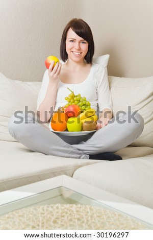 Young woman sitting cross-legged and eating fruits - stock photo