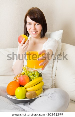 Young woman sitting cross-legged and eating fruits and drinking orange juice - stock photo