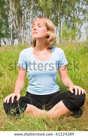 Young woman sitting cross-legged and relaxed - stock photo