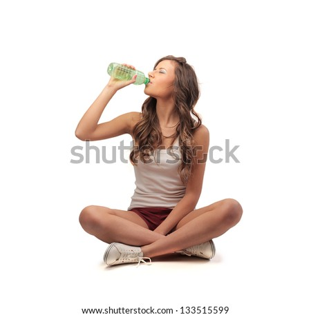 young woman sitting cross-legged drinking water from bottle - stock photo