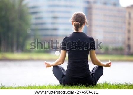 Young woman sitting cross legged on river bank in front of blue glass modern office building, meditating, practicing yoga Easy Pose, Sukhasana, asana for meditation, pranayama, breathing, back view - stock photo
