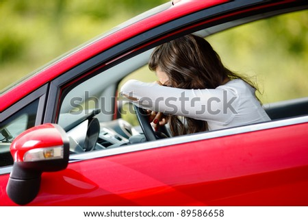 Young woman sitting depressed in car - stock photo
