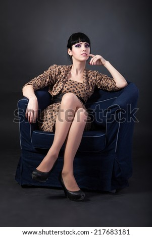 Young woman sitting in a blue armchair isolated over white - stock photo