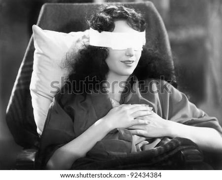 Young woman sitting in a chair with bandages over her eyes - stock photo